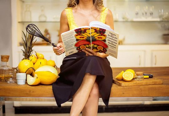 A girl sitting on table with holding a book