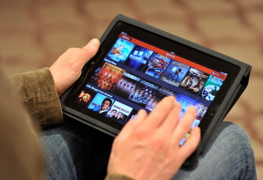 A Person Sitting and Watching Movies in Tablet